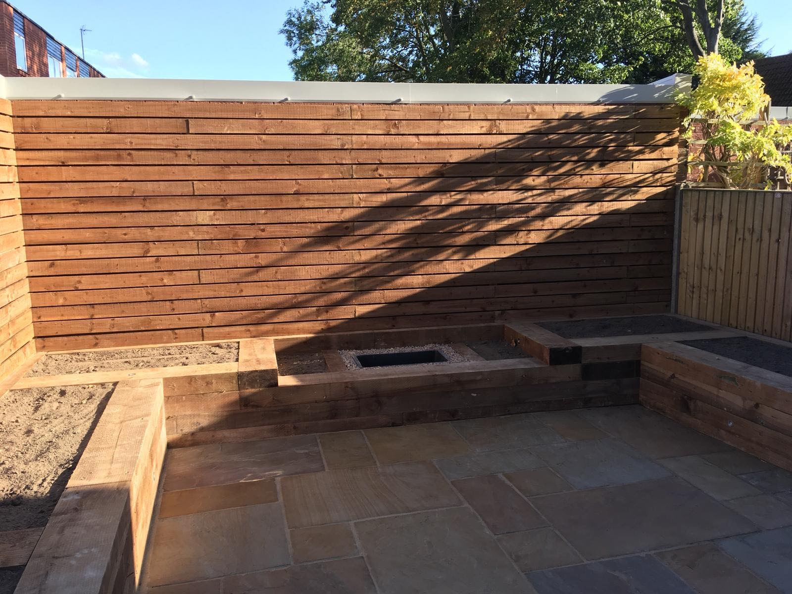 CONTEMPORARY WALL PANEL - RAILWAY SLEEPER RAISED BEDS - INDIAN SANDSTONE PAVING
