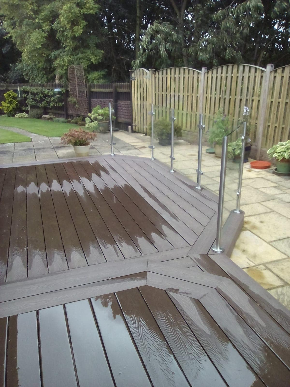 HERITAGE BROWN DEEP EMBOSSED COMPOSITE DECKING WITH GLASS BALUSTRADES AND STAINLESS STEEL POSTS